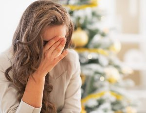 Stressed young woman in front of christmas tree