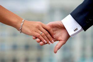 Wedding couple holding hands. Hands, rings, bracelets, cuff links, cuff closeup.